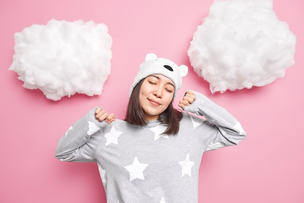 Girl closes eyes stretches in morning wears comfortable pajama and hat enjoys domestic atmosphere isolated on pink