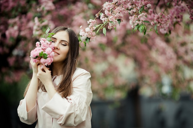 Girl closing her eyes smiles and holds a sakura branch