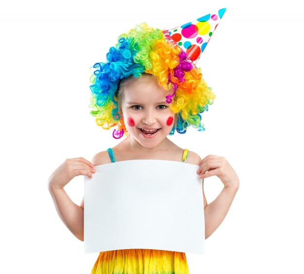 Girl in clown wig holds blank paper, isolated on white background