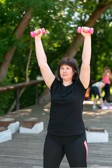 Девушка-тренер выполняет упражнения с гантелями в парке. фитнес на открытом воздухе. тренировка рук с гантелями. для начинающих