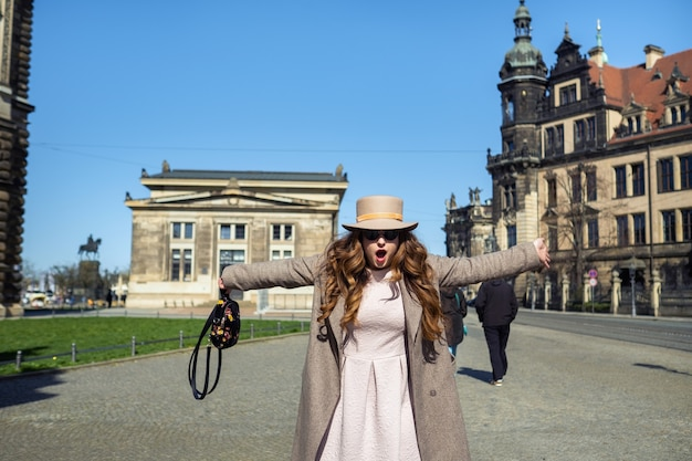 A girl in a coat and hat on a street in the city of dresden