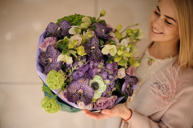 Girl in the coat holding a bouquet of purple violet and green flowers