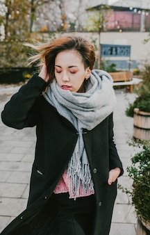 Girl in a coat and scarf posing on the street