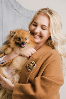 Girl in a coat with a brooch hugs a dog of the breed pomeranian spitz