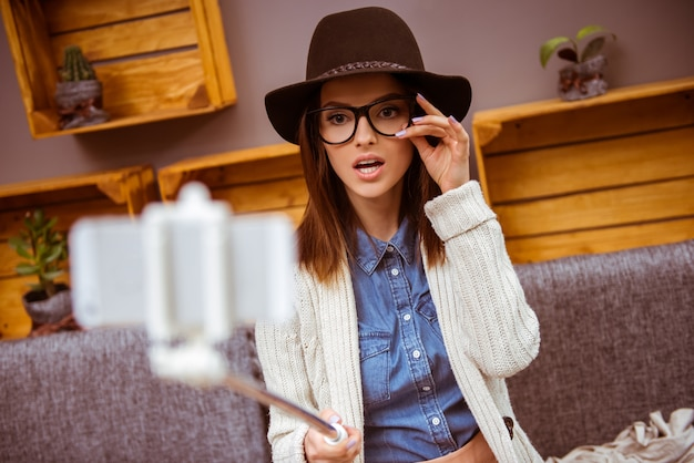 Girl in a coffee shop takes a selfie with glasses.