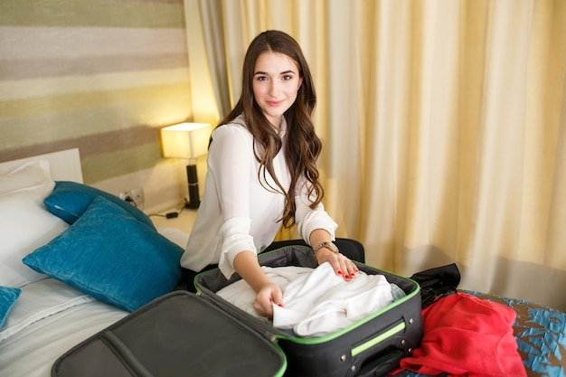 Girl collects clothes into a suitcase