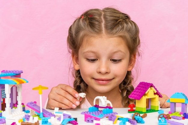 A girl collects a plastic construction kit on a pink background.