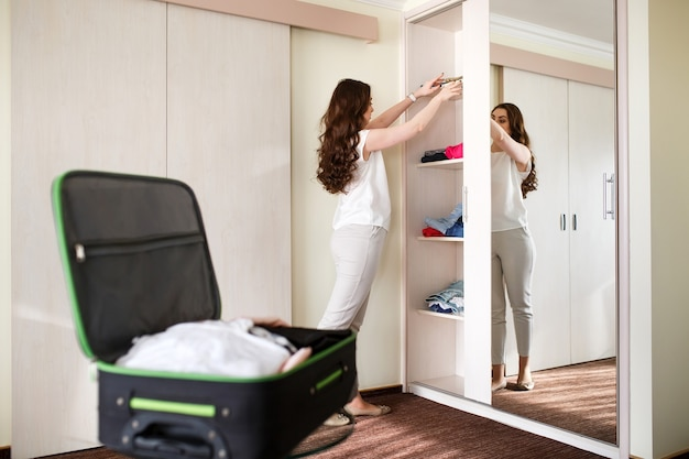 Girl collects a suitcase in a hotel room