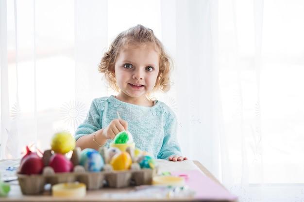 Girl coloring eggs and looking at camera