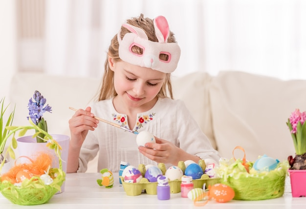 Girl coloring eggs in mask