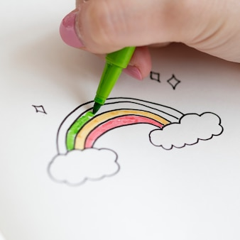 Girl coloring a rainbow doodle in a notebook