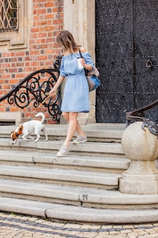 女の子は犬と一杯のコーヒーを持って階段を降りてきます