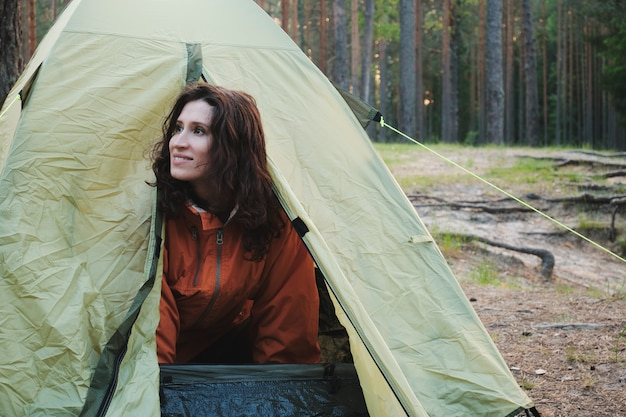 The girl comes out of the tent after sleeping. travel outside the city in the woods. camping.