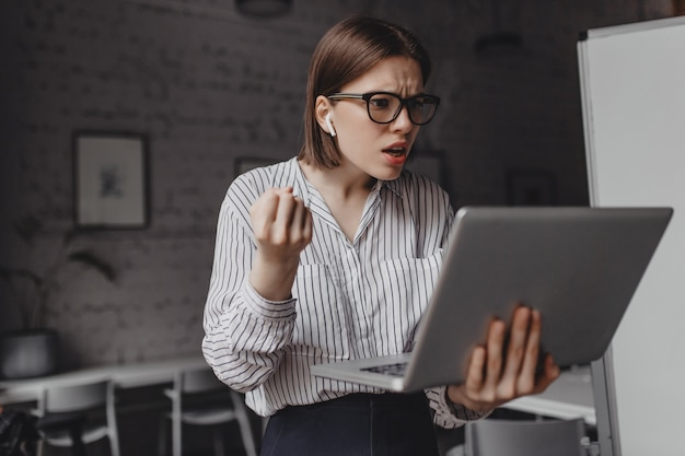 La ragazza comunica tramite video con indignazione. donna in camicetta bianca e occhiali in posa con il computer portatile nel suo ufficio.