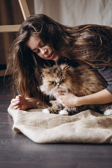 Girl communicates with her domestic red fluffy cat. love for animals.