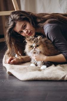 女の子は彼女の国内の赤いフワフワした猫と通信します。動物への愛。