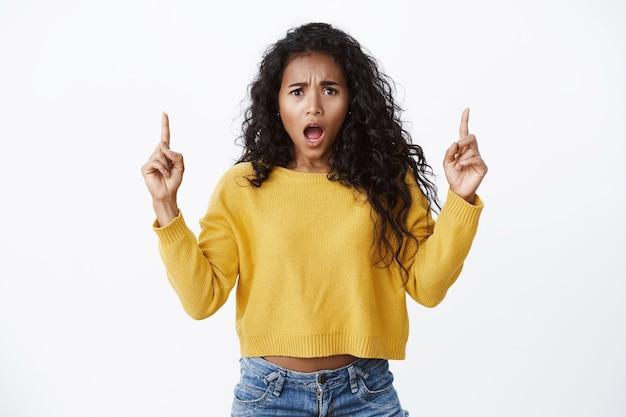 배신감과 속상함을 호소하는 소녀. 불쾌하고 화난 것처럼 보이는 노란 스웨터를 입은 아프리카계 미국인 곱슬머리 여성