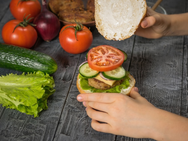 The girl completes the preparation of a delicious homemade hamburger with meat and vegetables