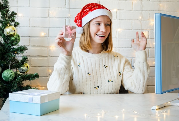 Girl at the computer communicates online and wishes merry christmas