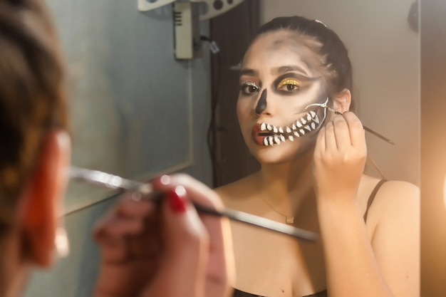 Girl concentrating on making up an artistic skull for halloween in her room.