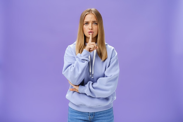 Girl concerned someone know secret making shush gesture with index finger over mouth begin not tell anyone with worried serious look staying shh crossing one arm against chest timid and insecure