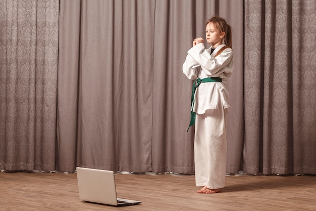 Girl conducts home training in karate in front of a laptop