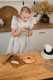 Девушка-кондитер делает фото кексов на смартфон. концепция ведения блога