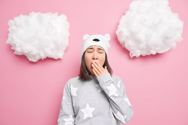 Girl cons mouth yawns wants to sleep has problem of insomnia dressed in nightwear soft bear hat isolated on pink