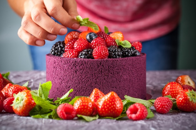 Girl cook a cake decorated with berries, strawberries, raspberries and mint