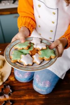 Девушка приготовила печенье для празднования рождества на кухне дома с рождеством и новым годом концепция кулинарии и праздника
