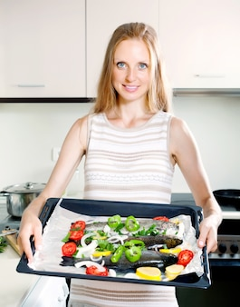 Girl cooking trout fish in pan
