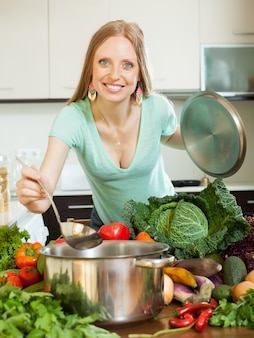 Girl cooking with vegetables in domestic kitchen