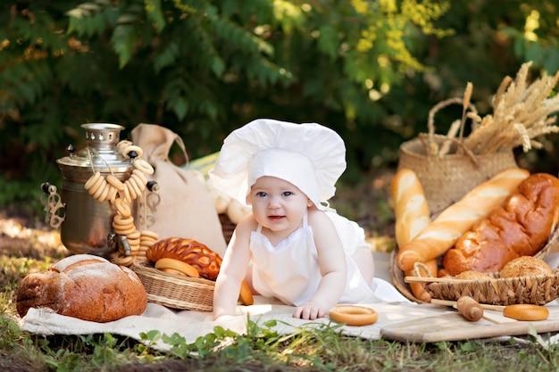 女の子は日当たりの良い夏の日に自然の中で調理します。幼児のパン屋は白いエプロンでパンとベーグルを食べる