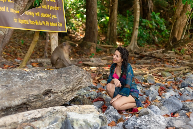 A girl in a cool swimsuit and pareo talking to monkeys on a tropical monkey beach.