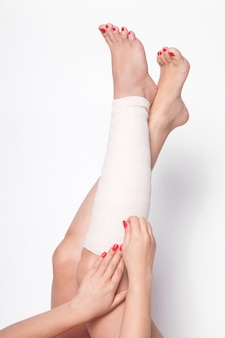 Girl corrects an elastic bandage on legs