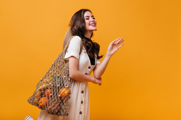 Ragazza in abito di cotone con bottoni marroni in posa su sfondo arancione con sacchetto di stringa.