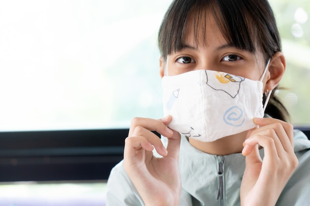 Girl under cotton face mask covering mouth and nose.