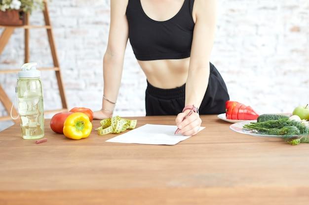 カロリーを数える女の子。若い女性は彼女のダイエット計画を使用します。減量とフィットネスのためのバランスの取れた食事