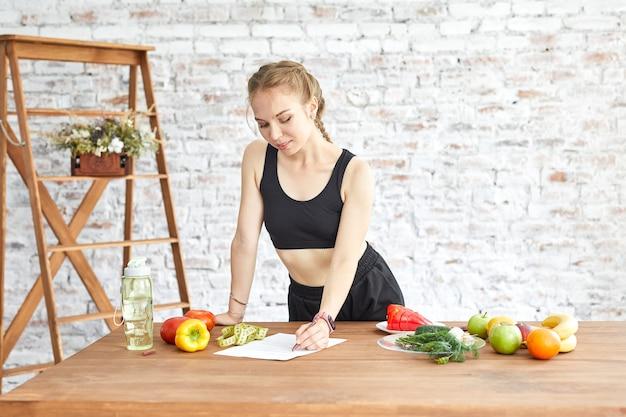 カロリーを数える女の子。若い女性は彼女のダイエット計画を使用します。減量とフィットネスのための健康的なライフスタイル