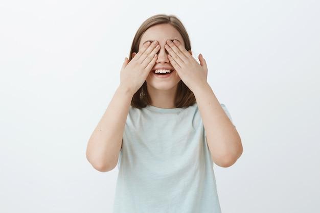 かくれんぼをしている間、友達を探す準備ができている10まで数える女の子。目を閉じて笑みを浮かべて手のひらで目を閉じて驚きを待っている水色のtシャツで楽しくて感情的なかわいい女性の肖像画