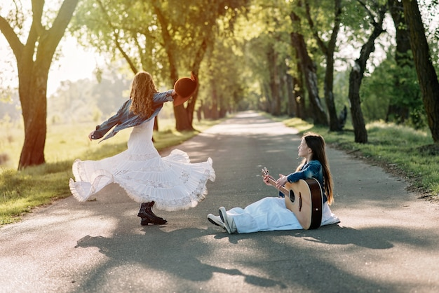 A girl in country-style clothes in a long dress dances on the road with a guitar at sunset. happy childhood.