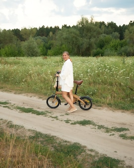 Girl in the countryside on a compact modern bike
