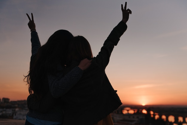 Girl couple celebrating love on a sunset