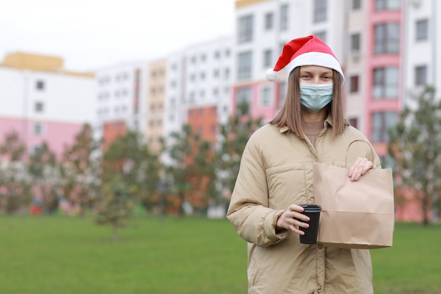 Girl courier in protective face mask and santa's hat holds a paper bag with products and a cup of coffee