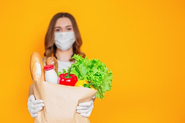 Девушка-волонтер-курьер в медицинской маске держит бумажный пакет с продуктами, овощами, травами, изолированными над оранжевой стеной, карантин, коронавирус, безопасная доставка еды, копия места для текста