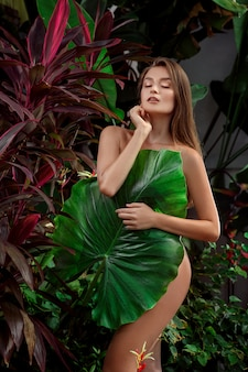 A girl cover her body with a huge green leaf.