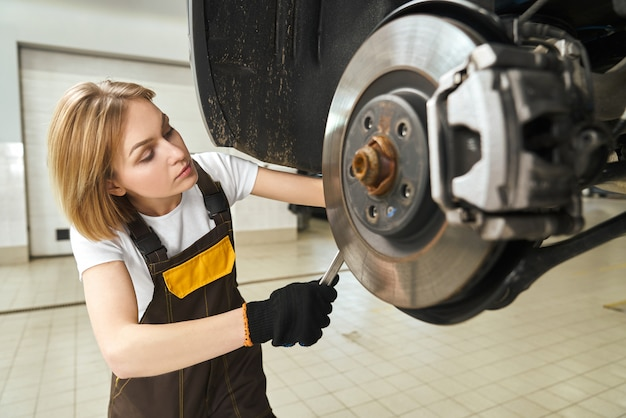 Girl in coveralls fixing car brake disk, using tool.