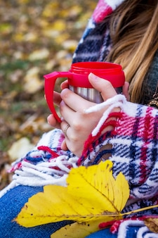 Girl covered with a blanket in the autumn forest holds a cup of tea in her hands