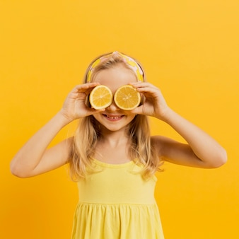 Girl covering eyes with lemon slices