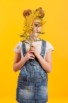 Girl covering face with flowers branches